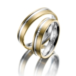Trouwringen geelgoud witgouden band. 3 diamanten van 0.005 ct
